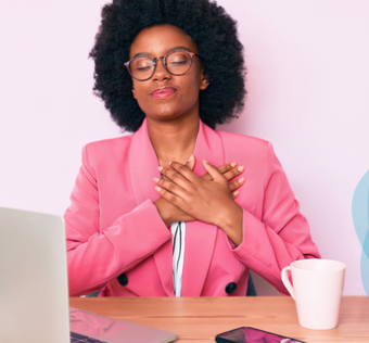 woman sits at her computer with a look of peace on her face as she holds her hands over her heart