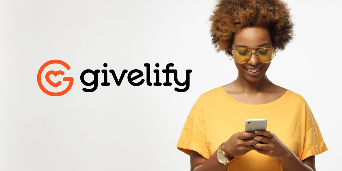 Black woman looks at her phone smiling, using Givelify