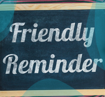 """Person holding sign with """"friendly reminder"""" written on it"""