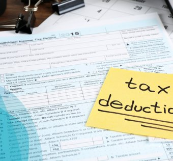 """Forms for filing taxes spread out on a desk with a yellow stick note that reads """"tax deductions"""""""